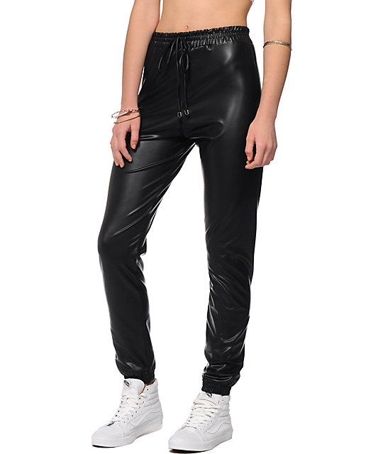 Lounge worthy black leather jogging pants are teamed with grey sleeveless top and patent pointy toes: Make some fun with bright purple garments and shoes: Keep it biker chic inspired by incorporating black leather jacket with grey pullover, simple jogging pants and trainers.
